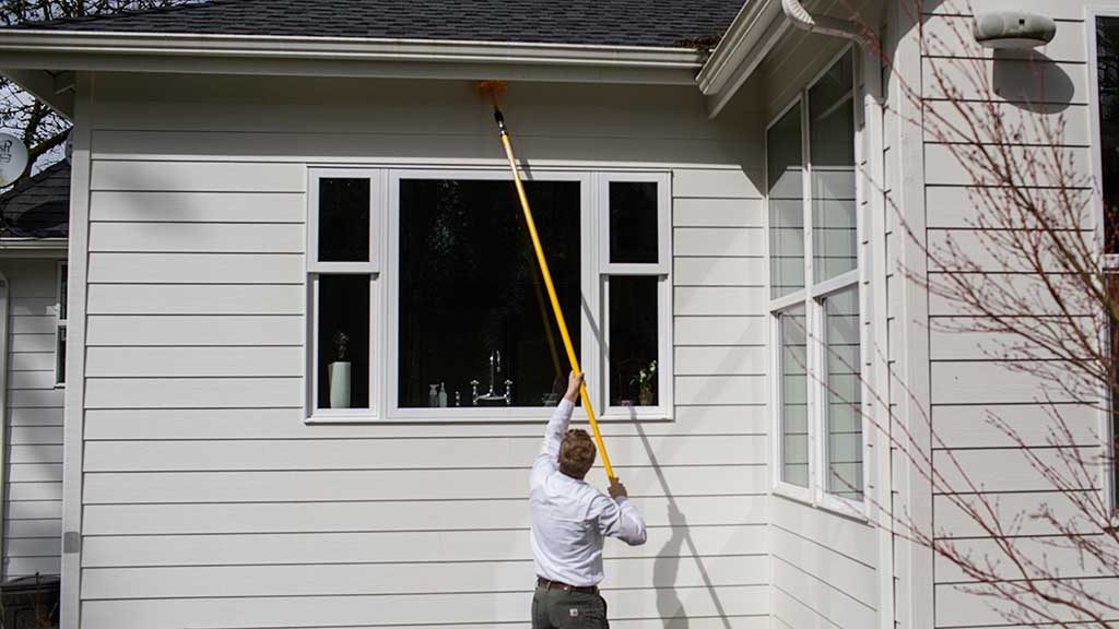 An exterminator is doing spider web removal in the eaves of a Vancouver Washington home.