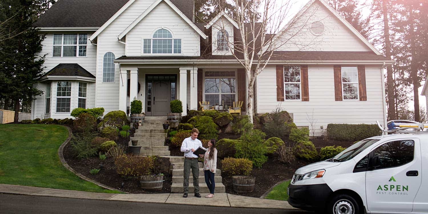 An exterminator is standing next to a customer just after a pest control treatment in Vancouver, WA