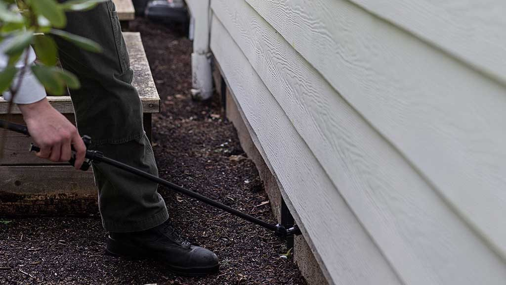 An exterminator is doing pest control under the siding of a home in Vancouver.