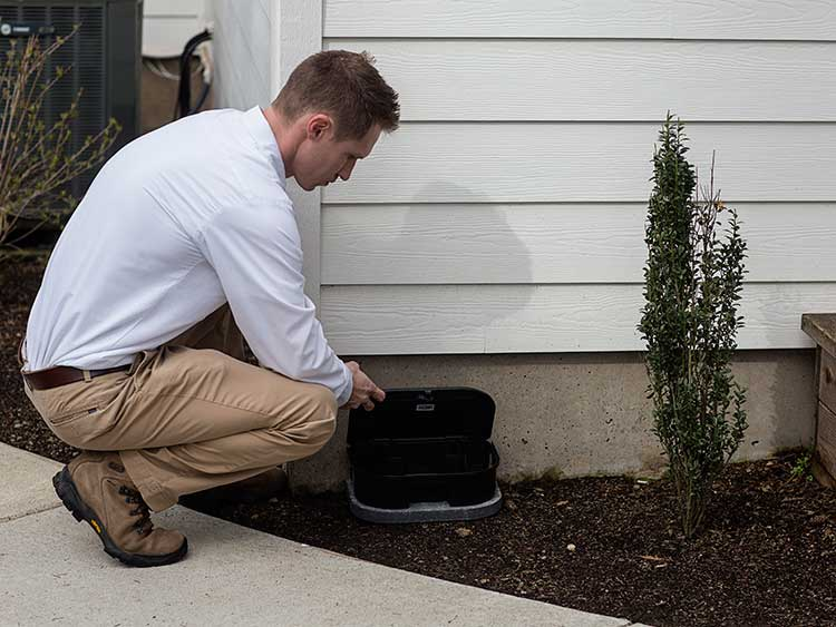 An exterminator adding a commercial grade bait station to the outside of home for rodent removal.