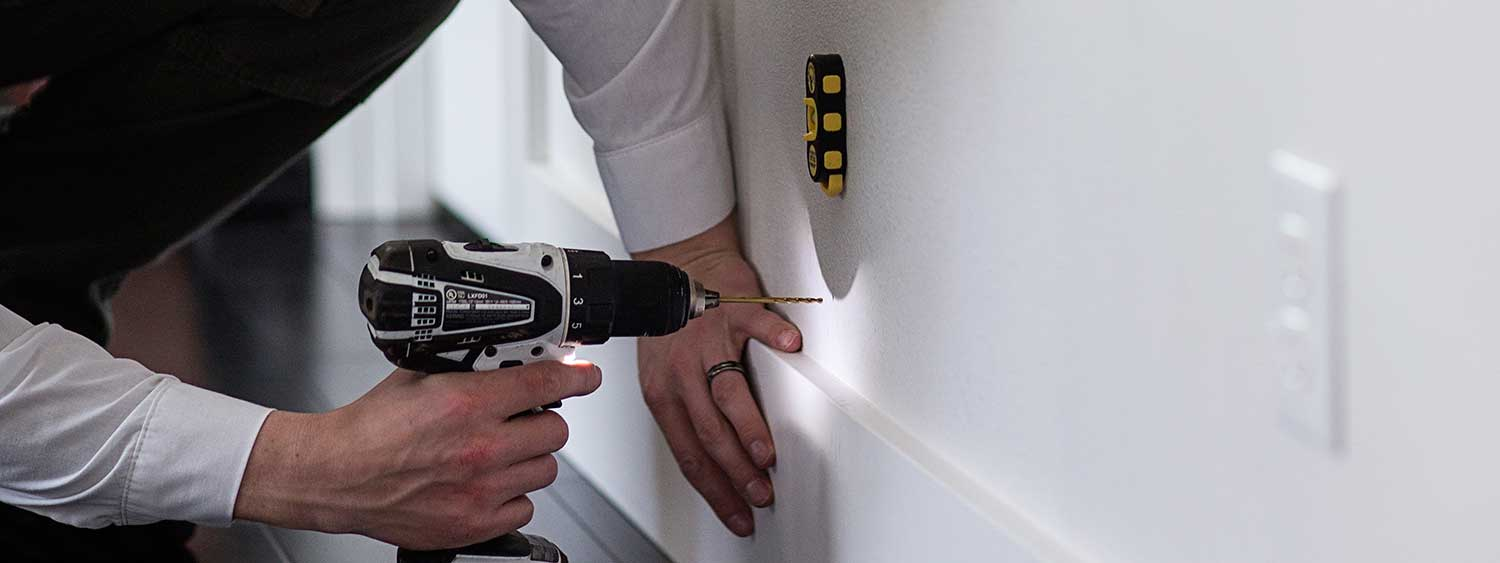 An Aspen Pest Control service technician drilling a tiny 1/8-inch hole in the wall for a foam injection at a home in Camas, WA