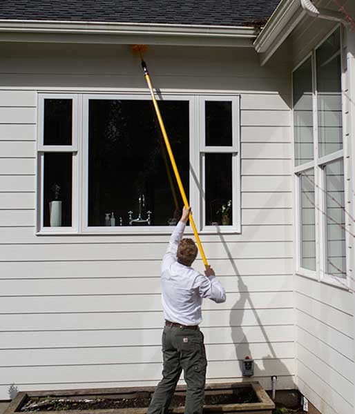 A pest control professional doing spider web removal at a home in Vancouver, WA.