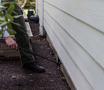 An exterminator treating bees at an entry point under the siding of a home in Vancouver, WA.