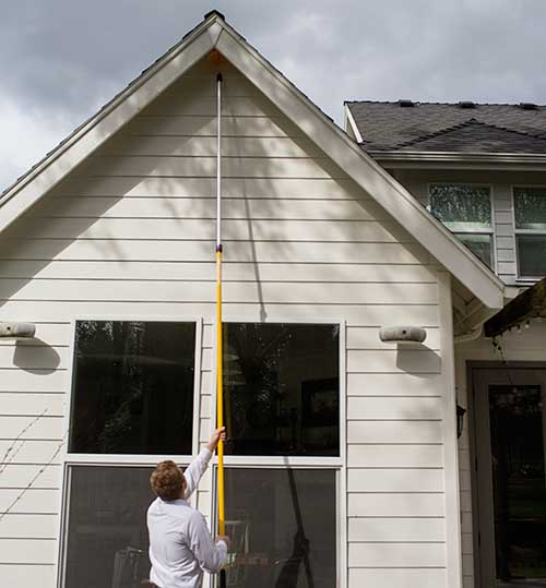 A pest control technician using an extension pole for wasp nest removal at a home in Vancouver, WA.