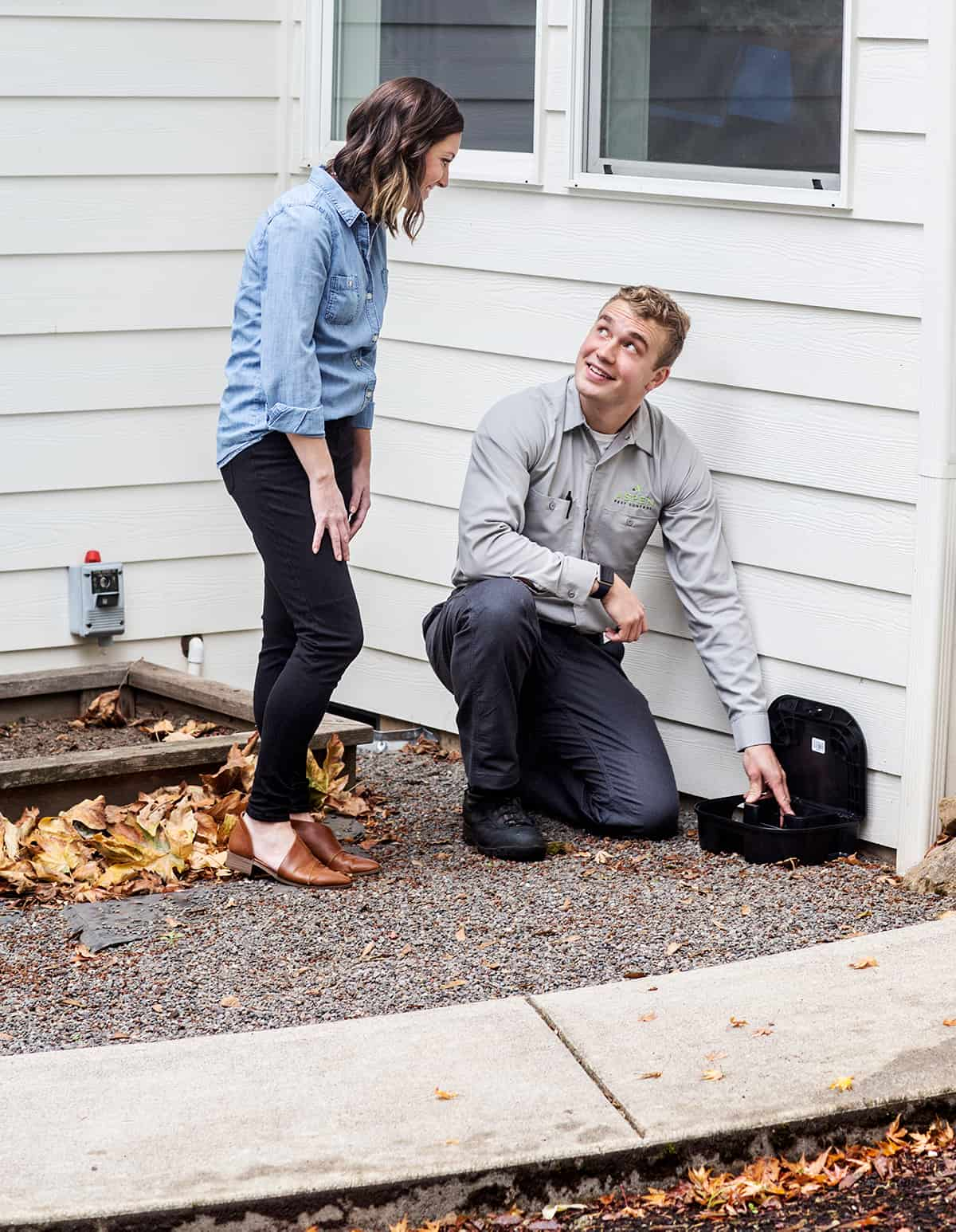 Aspen Pest Control Technician Setting Pest Bait Trap While Talking to Vancouver WA Homeowner